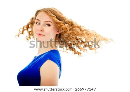 The beautiful blue-eyed girl with the flying red hair on a white background - stock photo