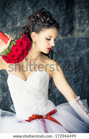 The beautiful bride is holding a bouquet of red roses. - stock photo