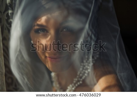 The beautiful bride stands near window