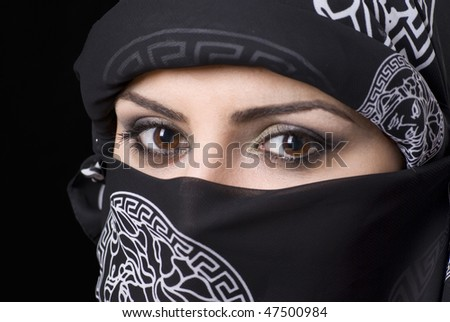 The beautiful brown eyes of an arabic woman with headscarf looking to camera. Focus on right eye. - stock photo