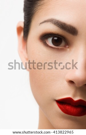 The beautiful brunette with evening cosmetics. Clean and smooth skin of the woman. Fashionable cosmetics.Bright shadows and lipstick. Cosmetology. Red chubby lips. Long eyelashes. Permanent make-up   - stock photo