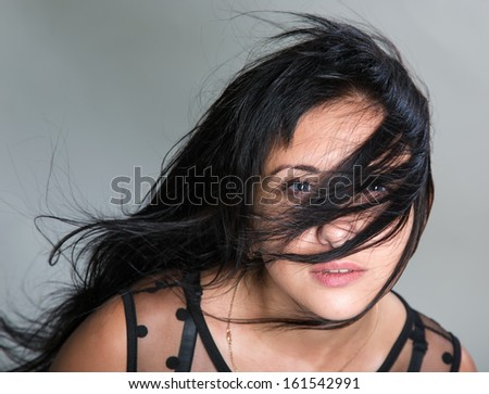 The beautiful brunette with fluttering hair - stock photo