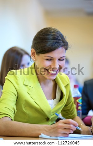 The beautiful brunette writes down and is laughs - stock photo