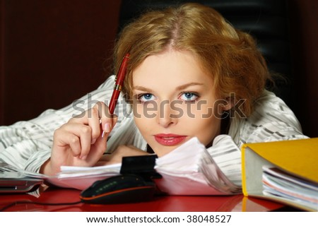 The beautiful business woman sits on a workplace and thinks - stock photo