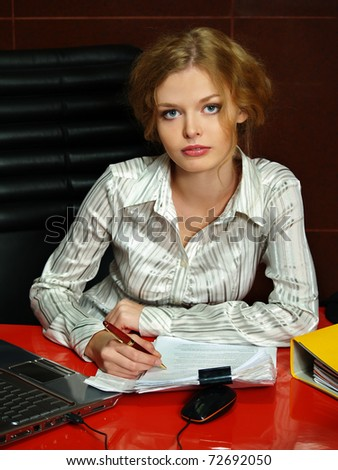 The beautiful business woman sits on a workplace and writes - stock photo