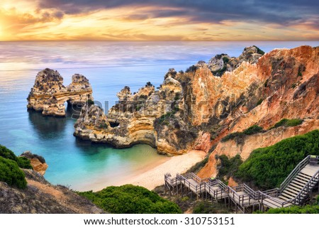 The beautiful Camilo Beach in Lagos, Portugal, with its magnificent cliffs and the blue ocean colorfully lit at sunrise - stock photo