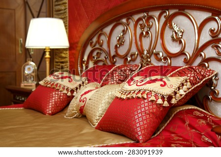 The beautiful embroidered pillows in a bed headboard in a bedroom - stock photo