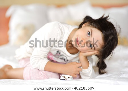 the beautiful European girl with dark hair in a light pajamas in a bed - stock photo