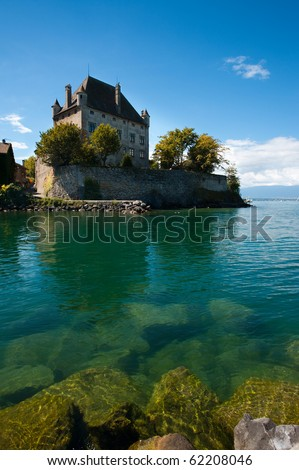 The beautiful floating French castle in Yvoire, France is anchored by partially submerged rocks and Lake Geneva's fresh waters. - stock photo