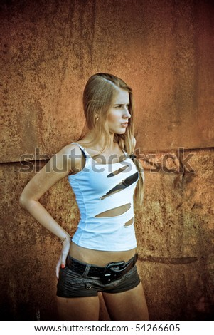 The beautiful girl costs at a rusty wall - stock photo