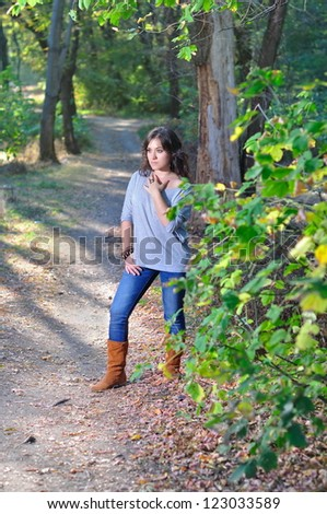 The beautiful girl costs on a footpath in the wood - stock photo