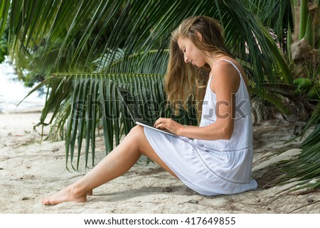 The beautiful girl from computers on the beach, in a white dress with palm trees, work behind the laptop