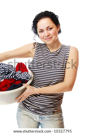 The beautiful girl holds a basin with clothes - stock photo