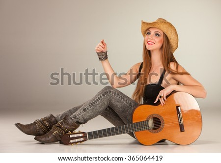 The beautiful girl in a cowboy's hat and acoustic guitar. - stock photo