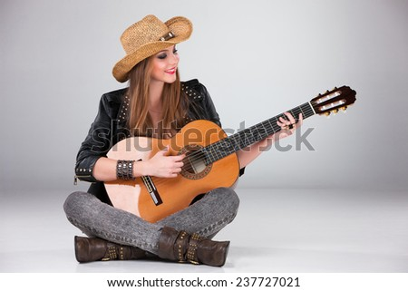 The beautiful girl in a cowboy's hat playing acoustic guitar on a gray background - stock photo