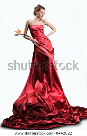 The beautiful girl in a long red dress holds an exotic flower in a hand - stock photo