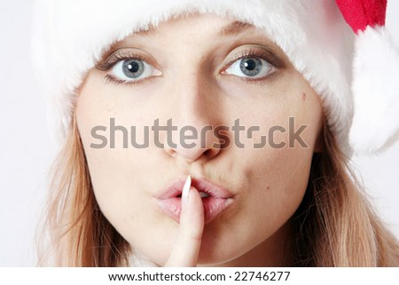 The beautiful girl in a New Year's cap holds a finger at lips - stock photo