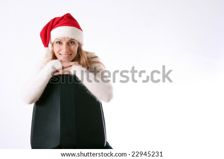 The beautiful girl in a New Year's cap sits on a chair - stock photo