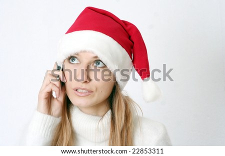 The beautiful girl in a New Year's cap speaks by phone