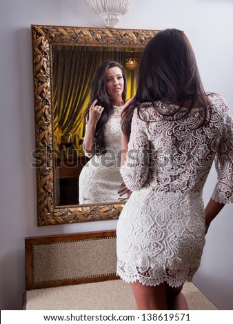 The beautiful girl in a short white dress looking into mirror .Young beautiful woman wearing a white short dress in the old hotel. Sensual Elegant young woman in white dress holding a wine glass - stock photo