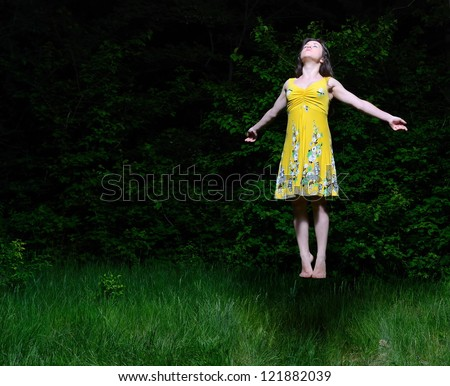 The beautiful girl in a summer dress flies on the wood - stock photo