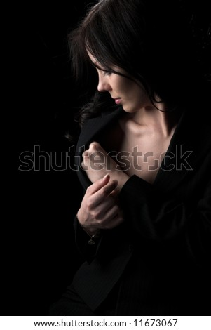 The beautiful girl in an evening dress on a black background