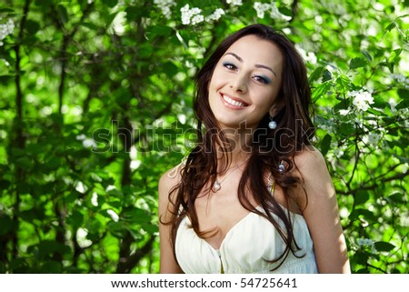 The beautiful girl in greens of trees - stock photo