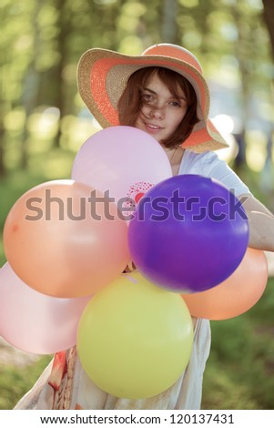 The beautiful girl in park with spheres - stock photo