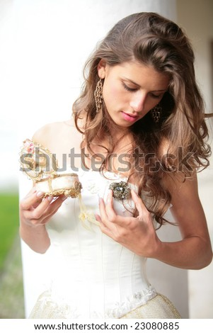 the beautiful girl in white-golden gown look at the gift - stock photo
