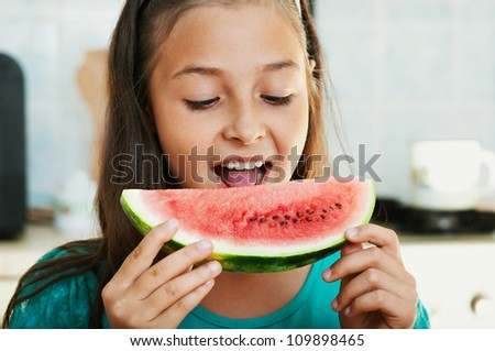 The beautiful girl is eating the watermelon