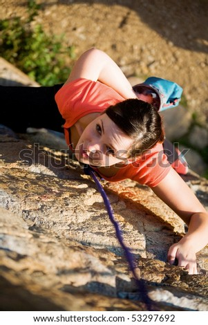 The beautiful girl is engaged in rock-climbing on a vertical rock - stock photo