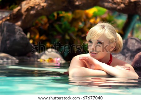 The beautiful girl lies in water with flowers - stock photo