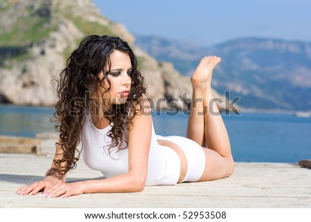 The beautiful girl lies on a pier near the sea