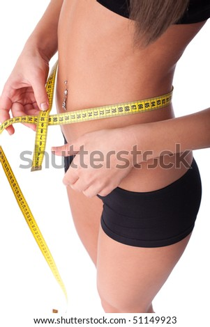 The beautiful girl measures a waist on a white background.  Healthy lifestyles concept. - stock photo