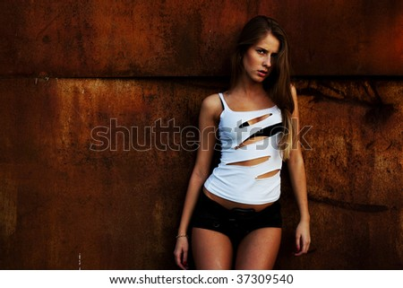 The beautiful girl model at a rusty wall - stock photo