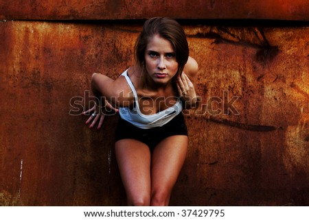 The beautiful girl model at a rusty wall