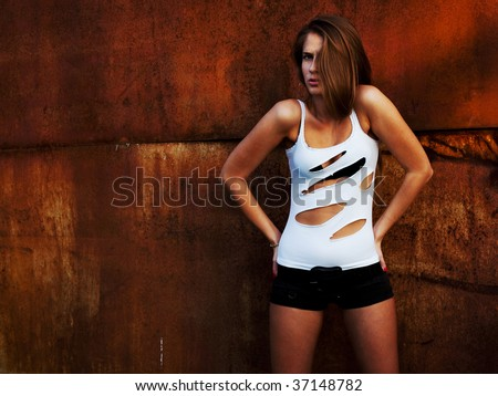 The beautiful girl model costs at a rusty wall - stock photo