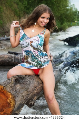 The beautiful girl on a coast of the river - stock photo