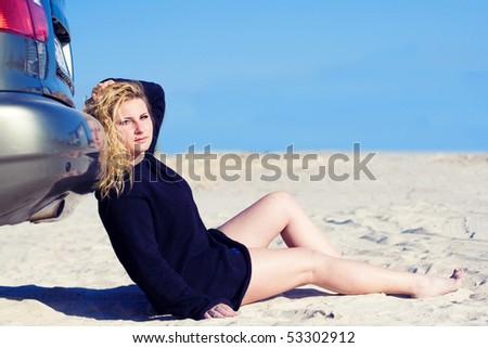 The beautiful girl on sand near the car - stock photo