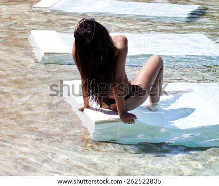 The beautiful girl poses in water.  - stock photo