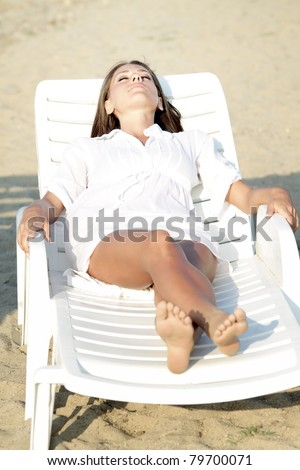 The beautiful girl relaxes in a deckchair on the beach