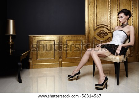 The beautiful girl sits in an armchair in a magnificent interior - stock photo