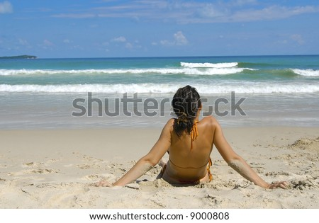 The beautiful girl sitting a back on a beach