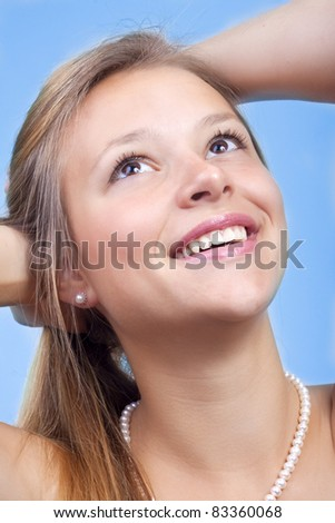 The beautiful girl smiles against the blue sky. - stock photo