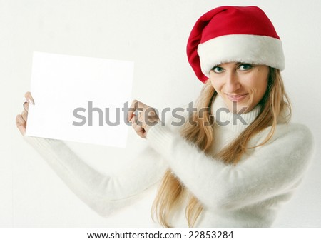 The beautiful girl smiles in a New Year's cap and holds white sheet