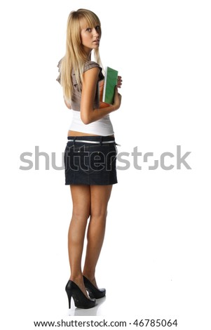 The beautiful girl stand with coloured writing-books and laptop on a white background. The student. - stock photo
