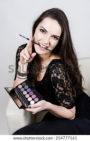 The beautiful girl wear black t-shirt with palette eyeshadow and brush