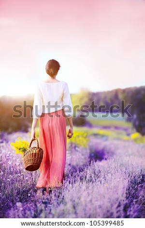 the beautiful girl with a flowers basket walks - stock photo