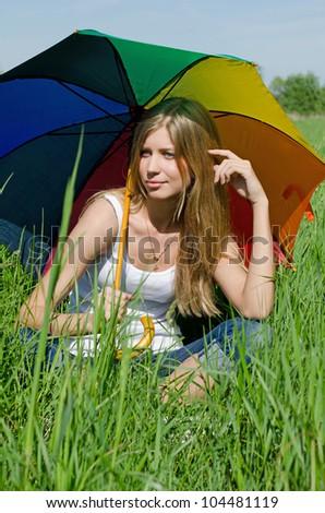 The beautiful girl with a multi-coloured umbrella - stock photo