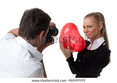 The beautiful girl with a red heart poses for the young guy on a white background. Selective focus on photographer. - stock photo